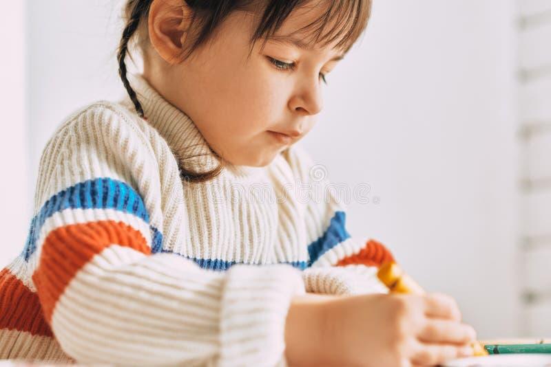 Retrato de la imagen del primer de la niña linda creativa que juega con los lápices del aceite, sentándose en el escritorio blanc fotos de archivo