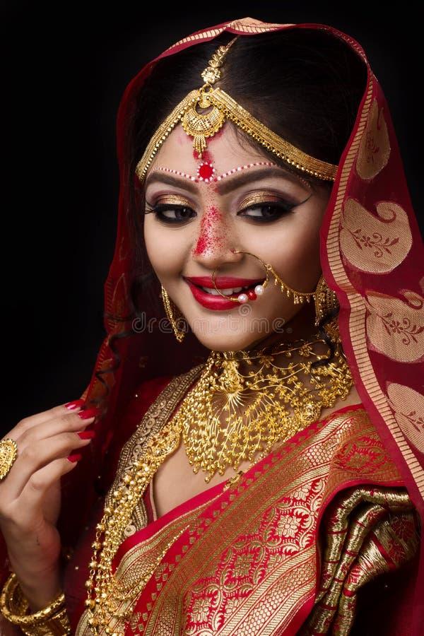 Retrato de la joyería del oro de la novia que lleva india joven y de la sari roja en la boda imagenes de archivo