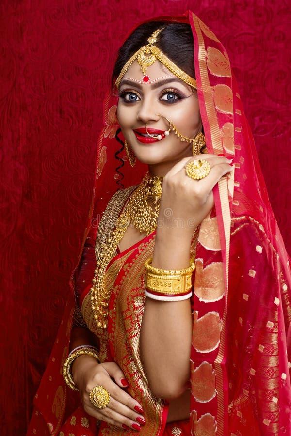 Retrato de la joyer?a del oro de la novia que lleva india joven y de la sari roja en la boda fotografía de archivo libre de regalías