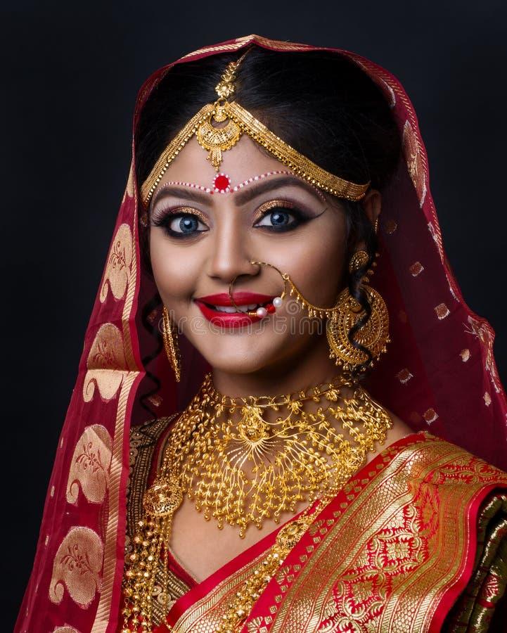 Retrato de la joyer?a del oro de la novia que lleva india joven y de la sari roja en la boda imagenes de archivo