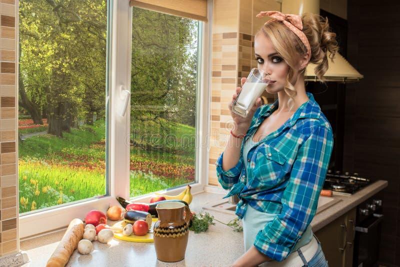 Retrato de la leche de consumo del ama de casa rubia magnífica en la cocina Frutas y verduras en la tabla imagen de archivo