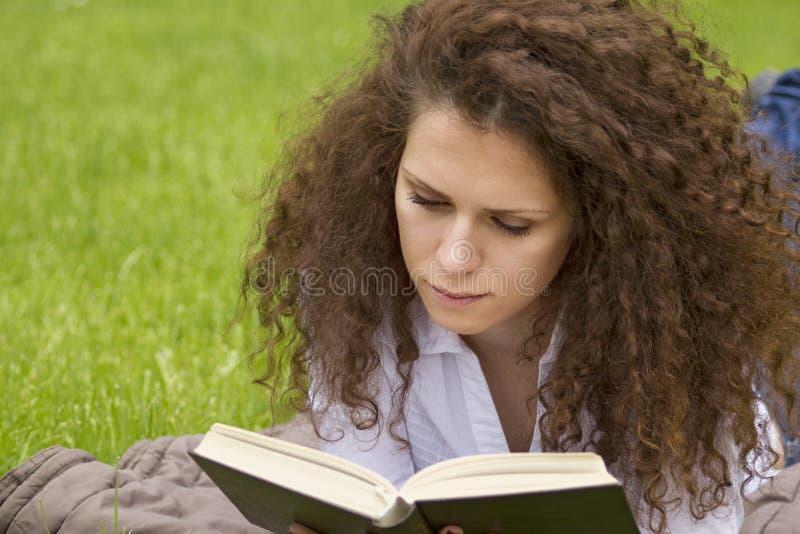 Retrato de la lectura relajada del aire libre del estudiante feliz imagenes de archivo