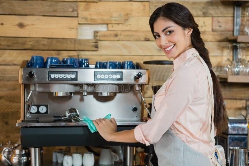 Retrato de la máquina de la cafetera de la limpieza de la camarera foto de archivo libre de regalías