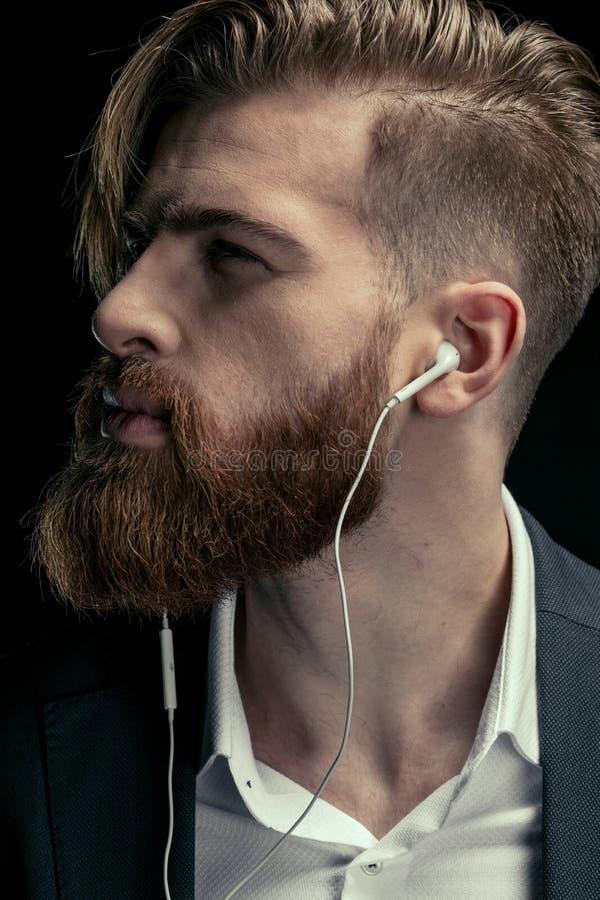 retrato de la música que escucha del hombre elegante con los auriculares imagenes de archivo