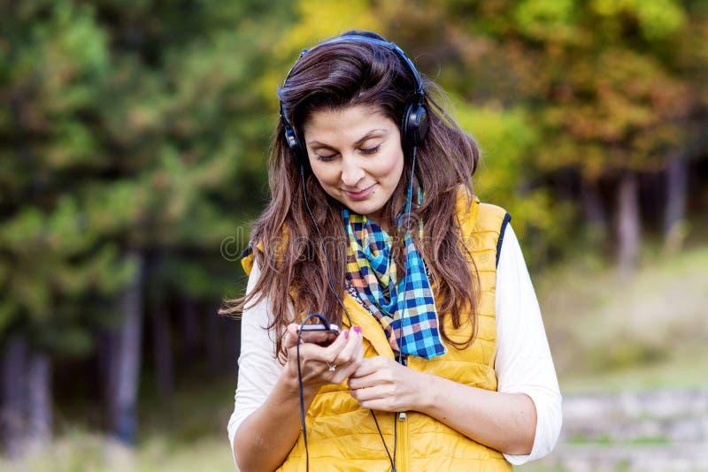 Retrato de la música que escucha hermosa de la mujer joven al aire libre Disfrutar de música foto de archivo