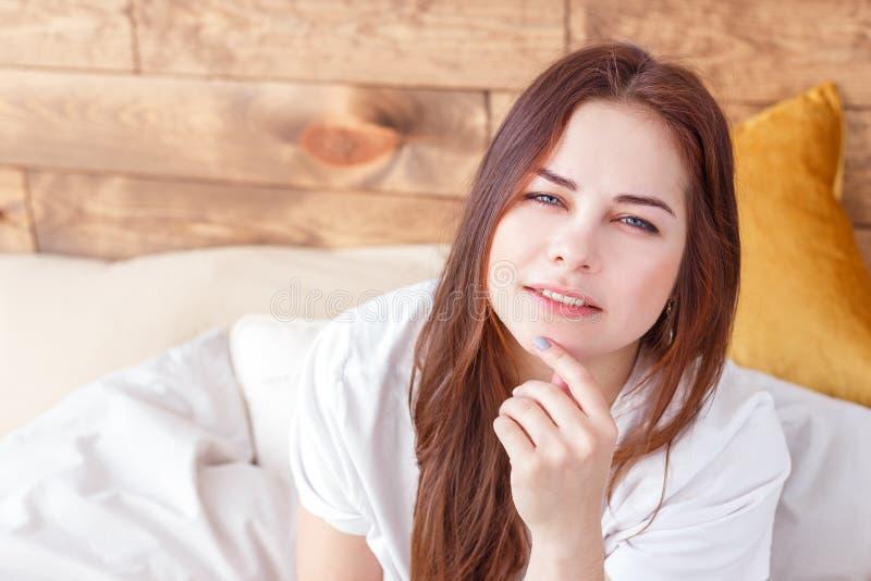 Retrato de la mañana de la mujer bonita pensativa joven que se relaja solamente en cama foto de archivo