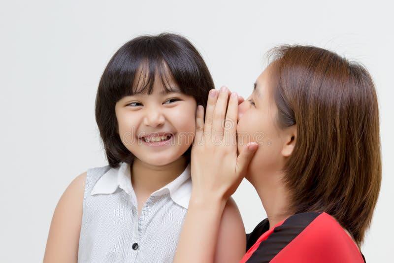 Retrato de la madre asiática que susurra a su hija fotografía de archivo libre de regalías