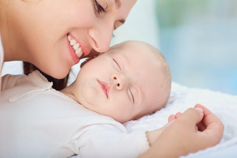 Retrato de la madre con su bebé que duerme en la cama foto de archivo libre de regalías