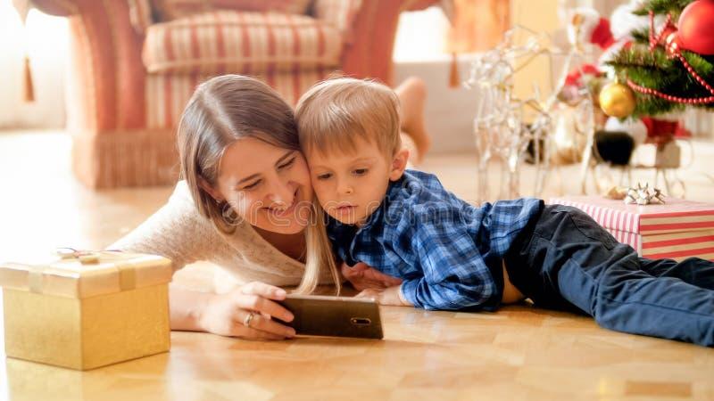 Retrato de la madre feliz sonriente con el niño pequeño que miente en la sala de estar bajo el árbol de navidad y vídeo de observ fotografía de archivo