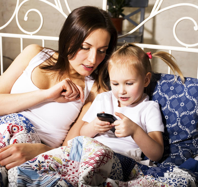 Retrato de la madre feliz y de la hija que ponen en cama y la observación imagen de archivo
