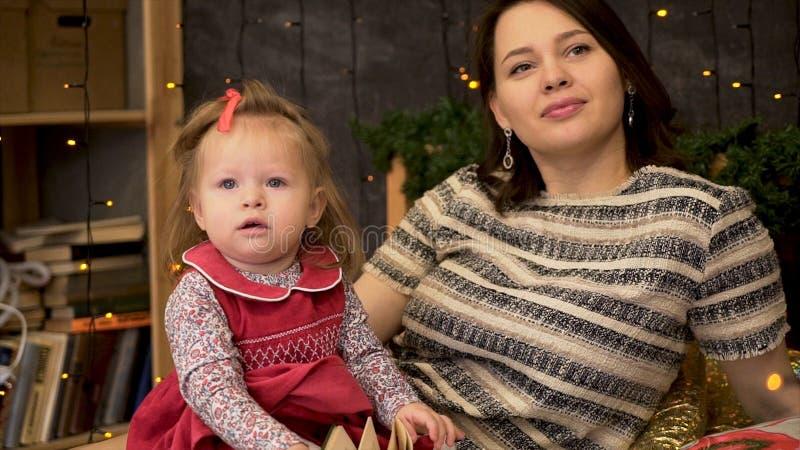 Retrato de la madre feliz y del bebé adorable en el cuarto adornado con las ramas y las guirnaldas verdes de la picea Mamá y lind foto de archivo