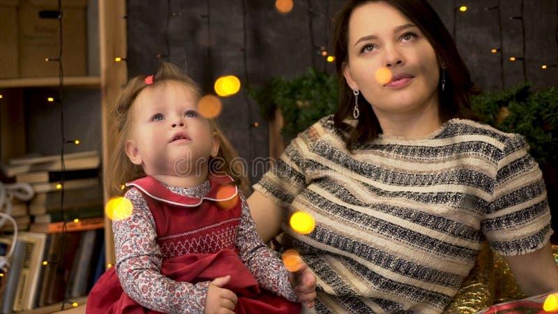 Retrato de la madre feliz y del bebé adorable en el cuarto adornado con las ramas y las guirnaldas verdes de la picea Mamá y lind foto de archivo libre de regalías