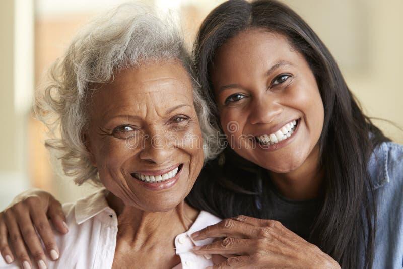 Retrato de la madre mayor que es abrazada por la hija adulta en casa foto de archivo