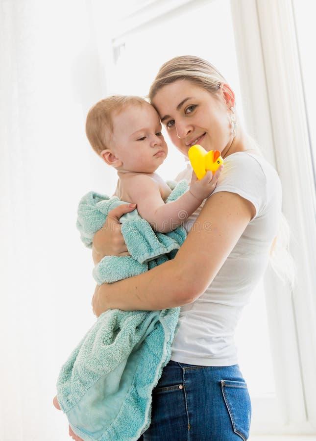 Retrato de la madre que cuida joven hermosa que celebra a su bebé en toalla azul después de lavarse en baño imágenes de archivo libres de regalías