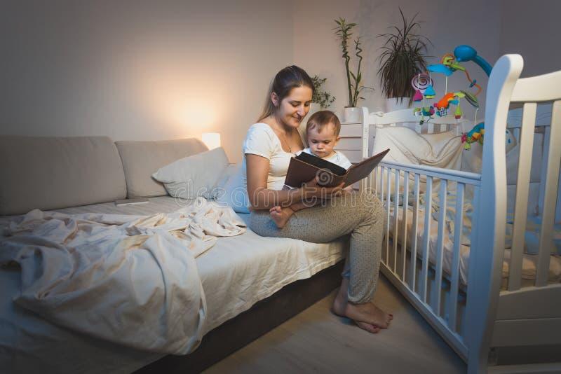 Retrato de la madre que detiene al bebé en rodillas y que lo lee un b foto de archivo