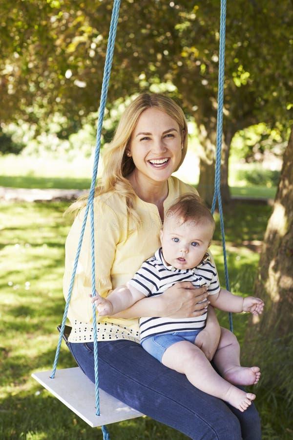 Retrato de la madre que juega con el hijo del bebé en el oscilación del jardín fotografía de archivo