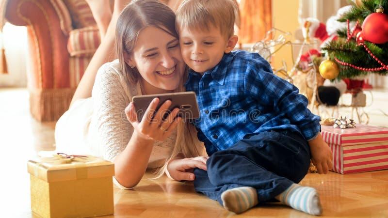 Retrato de la madre sonriente alegre con el bebé que miente en piso en la sala de estar y el vídeo de observación en el teléfono  foto de archivo libre de regalías