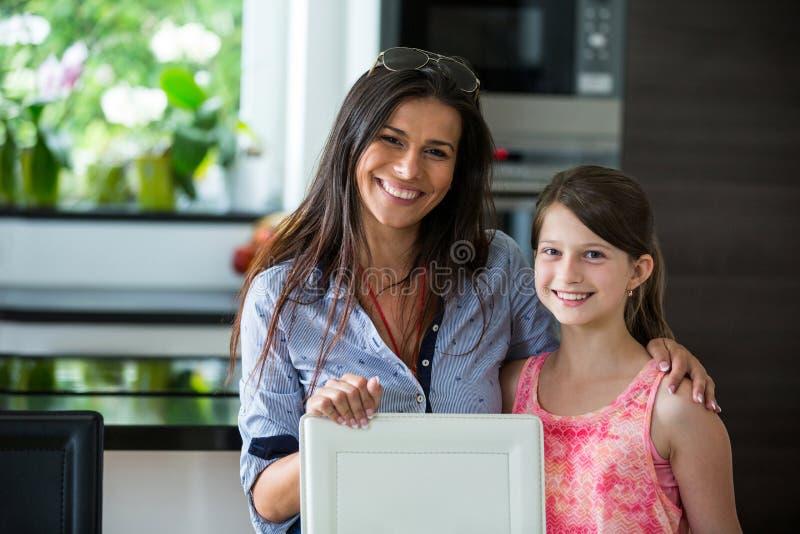 Retrato de la madre y de la hija junto en sala de estar foto de archivo libre de regalías