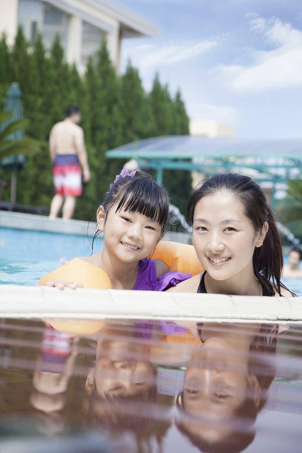 Retrato de la madre y de la hija sonrientes en la piscina por el borde que mira la cámara fotografía de archivo