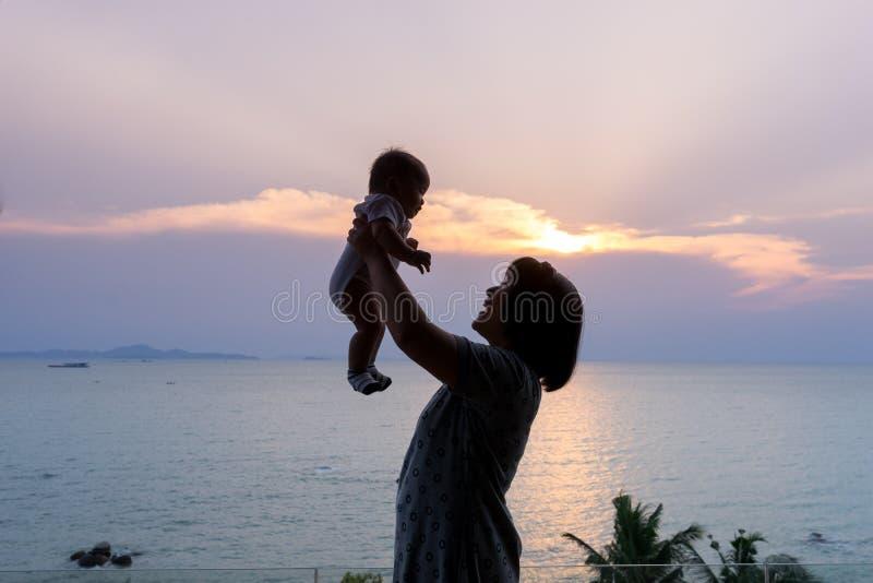 Retrato de la madre y del bebé asiáticos en la playa foto de archivo libre de regalías