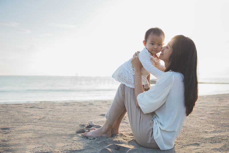 Retrato de la madre y del bebé en la playa en la puesta del sol fotografía de archivo libre de regalías