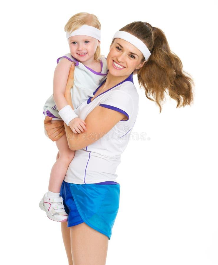 Retrato de la madre y del bebé felices en ropa del tenis fotos de archivo libres de regalías
