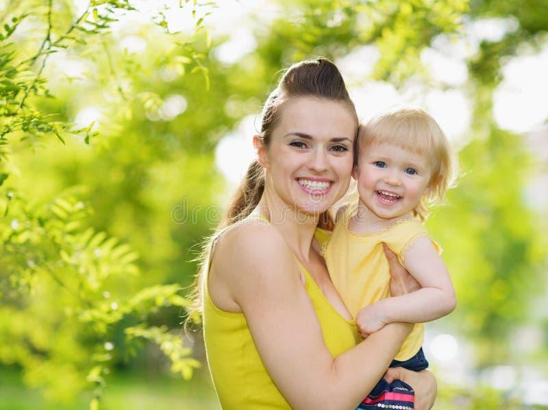 Retrato de la madre y del bebé sonrientes al aire libre fotografía de archivo