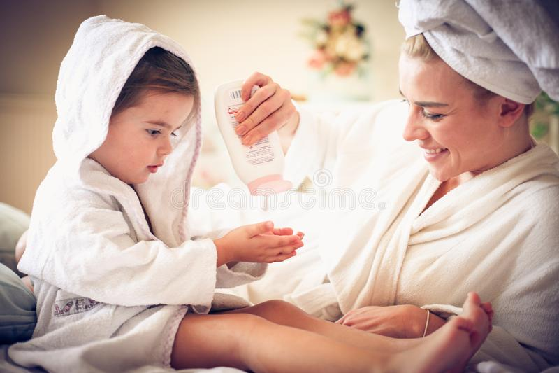 Retrato de la madre y de la hija después del baño que aplica la loción del cuerpo imágenes de archivo libres de regalías