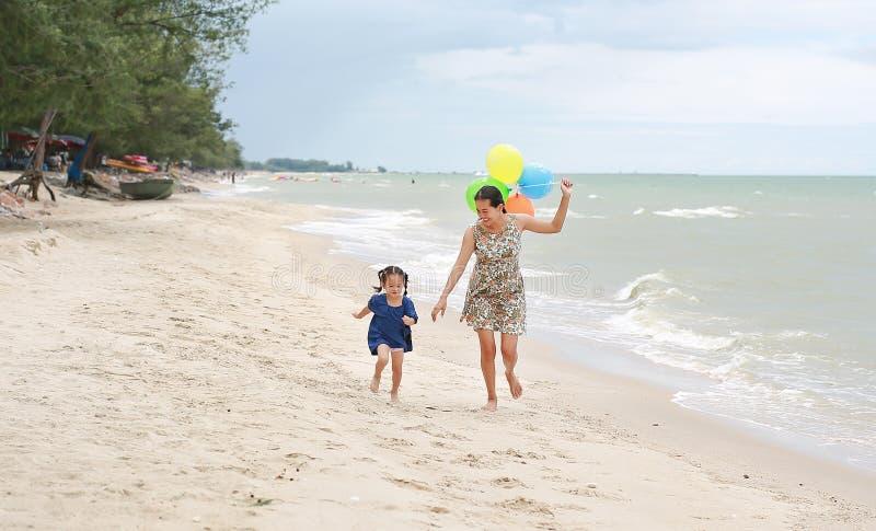 Retrato de la madre y de la hija que corren en la playa con los globos coloridos en mano de la madre Concepto del d?a de fiesta fotos de archivo