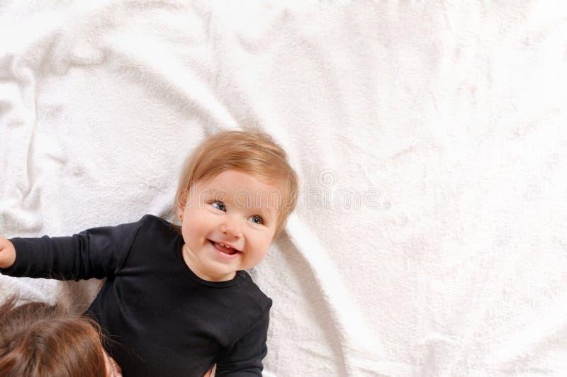 Retrato de la mamá hermosa que juega con su bebé en dormitorio imagenes de archivo