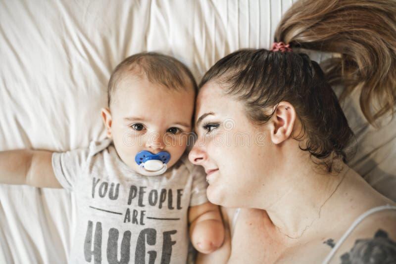Retrato de la mamá hermosa que juega con sus 8 meses del bebé en el dormitorio, visión superior imágenes de archivo libres de regalías