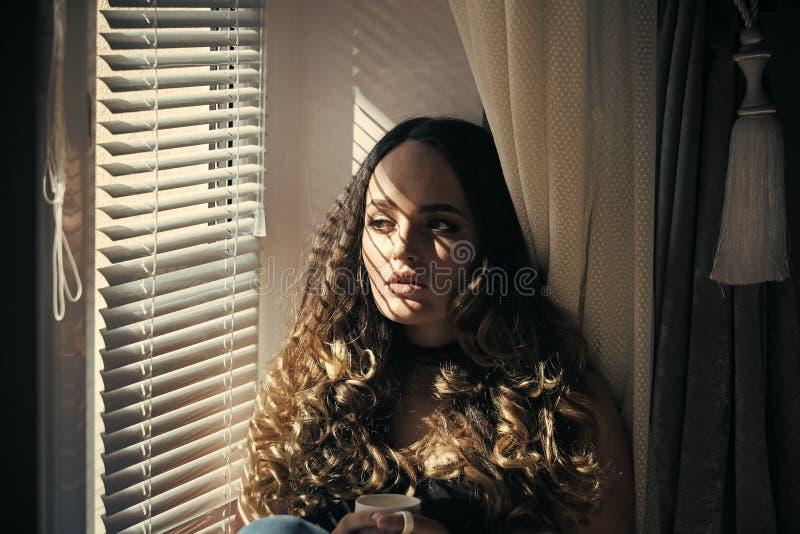 Retrato de la manera de la belleza Muchacha en la ventana con la taza de té o de café fotos de archivo