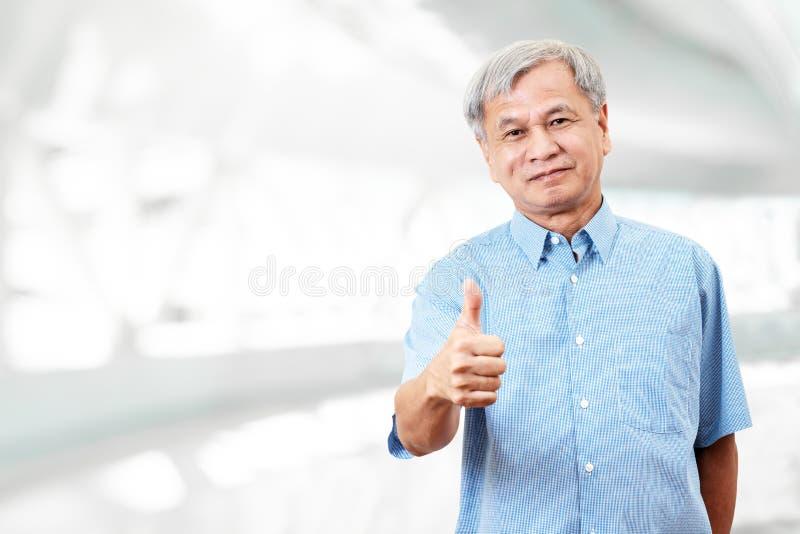 Retrato de la mano asiática mayor feliz del gesto del hombre que muestra el pulgar para arriba o la buena muestra y que mira la c fotos de archivo
