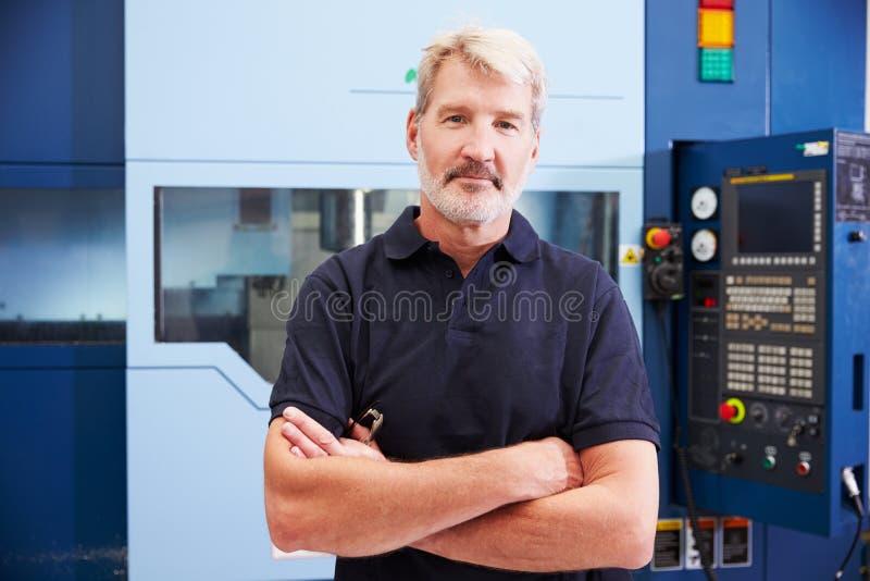 Retrato de la maquinaria masculina del CNC de Operating del ingeniero en fábrica foto de archivo libre de regalías
