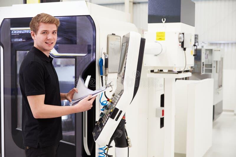 Retrato de la maquinaria masculina del CNC de Operating del ingeniero en fábrica fotografía de archivo libre de regalías