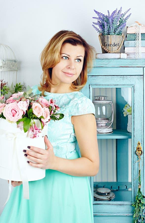 Retrato de la mediados de mujer adulta sonriente con la cesta o las rosas imagenes de archivo