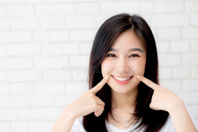 Retrato de la mejilla derecha del tacto del finger de la felicidad asiática joven hermosa de la mujer en fondo gris del ladrillo  foto de archivo
