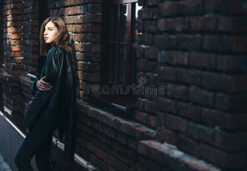 Retrato de la moda de la forma de vida de la muchacha morena en estilo del negro de la roca, colocándose al aire libre en la call foto de archivo
