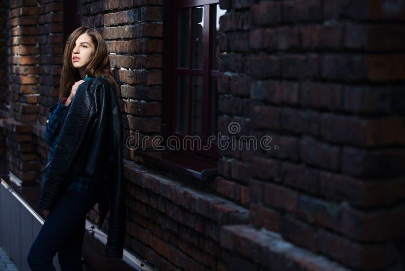 Retrato de la moda de la forma de vida de la muchacha morena en estilo del negro de la roca, colocándose al aire libre en la call fotos de archivo