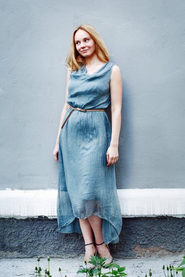 Retrato de la moda de la mujer joven cerca de la pared foto de archivo