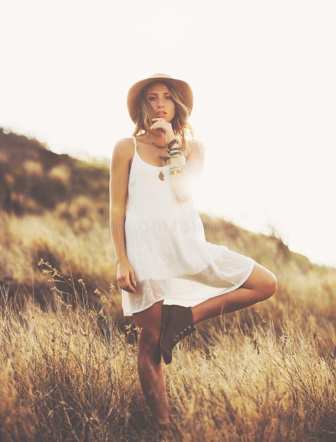 Retrato de la moda de la mujer joven hermosa hecha excursionismo en la puesta del sol imagenes de archivo