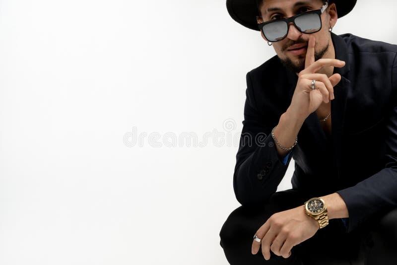 Retrato de la moda del hombre joven barbudo elegante en traje y sombrero de moda en lentes de sol negros, mostrando la muestra de fotografía de archivo libre de regalías