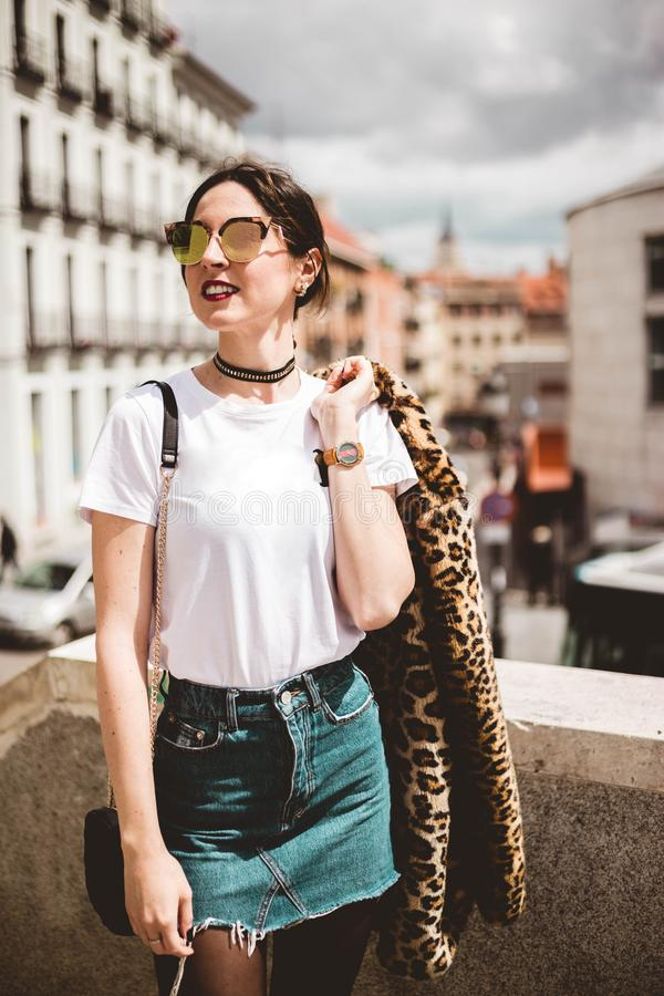 Retrato de la moda del modelo joven que sonríe y que lleva el animal de moda, falso abrigo de pieles del estampado leopardo, gafa imagen de archivo libre de regalías