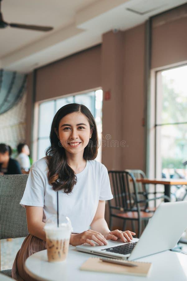 Retrato de la moda de la forma de vida de la chica joven bonita que trabaja en el ordenador portátil en el espacio abierto Caf? d fotos de archivo
