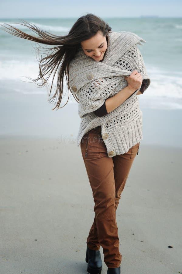 Retrato de la moda de la forma de vida de la primavera de la mujer elegante joven que camina en una playa del mar foto de archivo