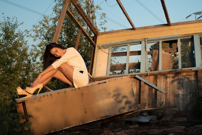 Retrato de la moda de la mujer joven, en una casa vieja, en la ruina, sentándose foto de archivo