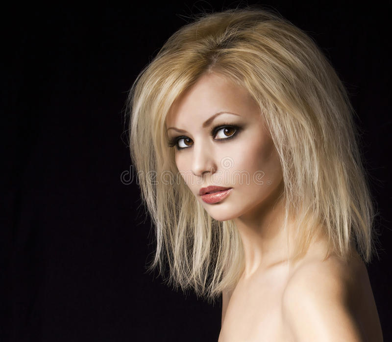 Retrato de la moda. Mujer rubia hermosa con maquillaje y el peinado profesionales, sobre negro. Modelo del estilo de Vogue imagen de archivo libre de regalías