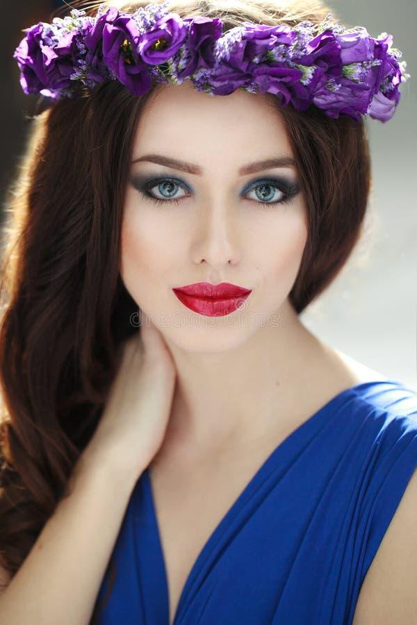 Retrato de la moda de una mujer joven de la morenita de la belleza con la corona de la flor del purpple El peinado y perfectos co foto de archivo libre de regalías