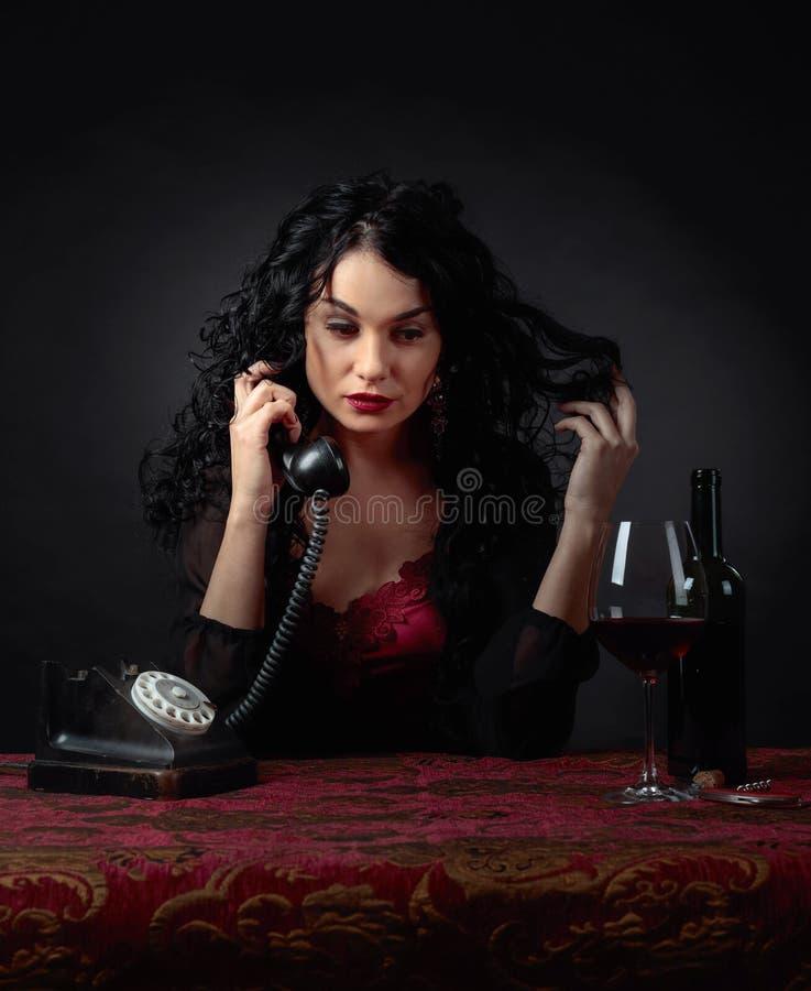 Retrato de la morenita atractiva con el teléfono y el vino tinto viejos fotos de archivo