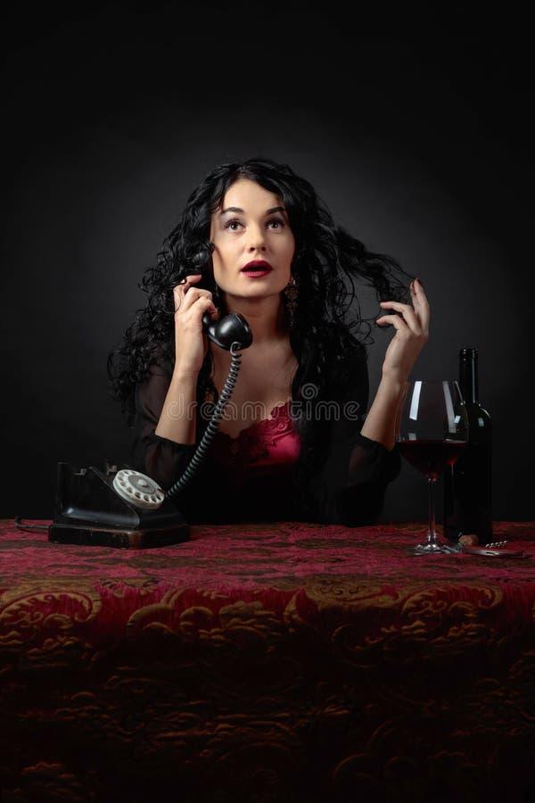 Retrato de la morenita atractiva con el tel?fono y el vino tinto viejos fotografía de archivo libre de regalías